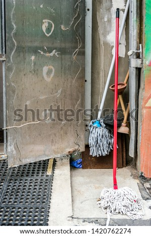 Open steel doorway on to alleyway where cleaning mops and plungers are being stored.