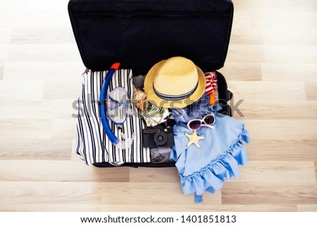 Open suitcase for vacation with clothing, hat, sunglasses, swimming mask and camera, travel and vacations concept. Opened bag with summer stuff, top view.