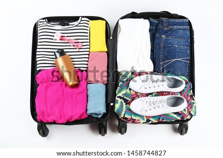 Open suitcase fully packed with folded women's clothing and accessories on the floor. Woman packing for tropical vacation concept. Female luggage w/ things. Background, close up, copy space, top view.