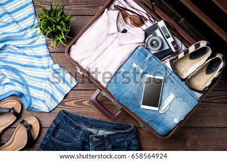 Open suitcase with casual female clothes on wooden table