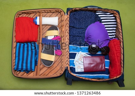 Open suitcase with things. Things collected for a vacation trip. #1371263486