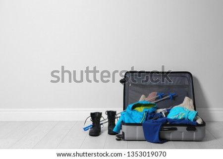 a1b6fc0cb3f Open suitcase with warm clothes for winter vacation on wooden floor. Space  for text