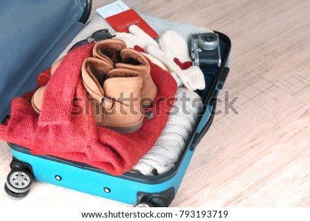 Open suitcase with warm clothes on wooden floor. Winter vacation concept #793193719