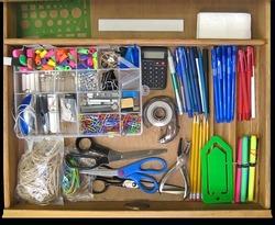 Open teacher's desk drawer full of supplies.