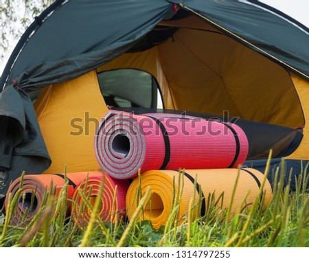 Open tent and rolled sleeping pads. Campsite. #1314797255