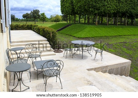 Open terrace with iron patio furniture and garden trees and lawn on the background, Gironde, France
