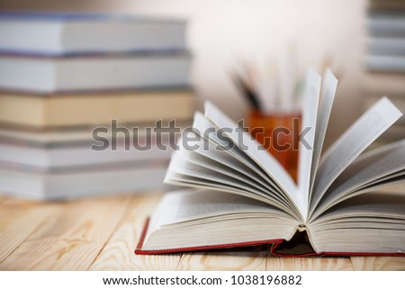 Open textbooks on wood desk with blurred focus for education background. Back to school concept #1038196882