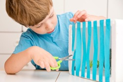 Open the cage. Liberation of animals. Fighting Animal Cruelty and Neglect. Boy cutting paper rods of the cage to liberate elephant. Implement to train fine motor skils, learning to cut with scissors.