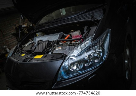 open the hood and engine of a modern car in the brick garage
