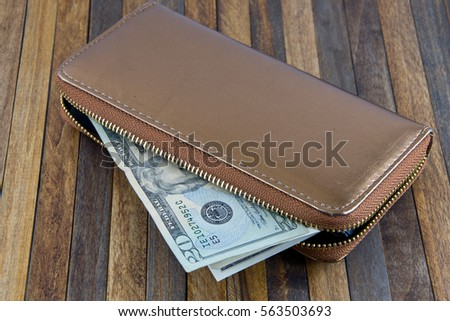 Open the purse and money sticking out. Photo taken on wooden background.