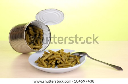 Open tin can and plate with french bean and spoon on wooden table on green background