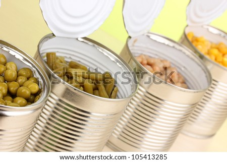Open tin cans of peas, corn, bean and french bean on wooden table on green background