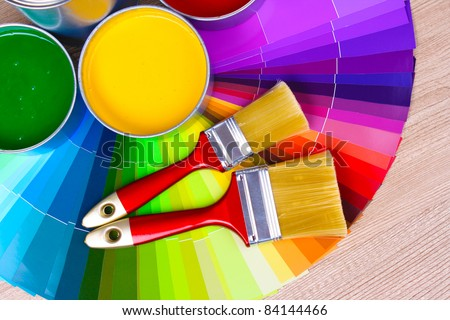 open tin cans with paint and palette on wooden background