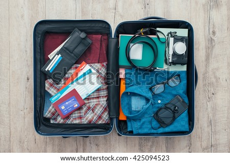 Open traveler\'s bag with clothing, accessories, credit card, tickets and passport, travel and vacations concept