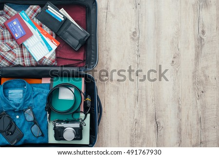 Open traveler\'s bag with clothing, accessories, credit card, tickets and passport, travel and vacations concept, flat lay
