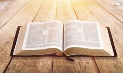 Open vintage christian bible on desk