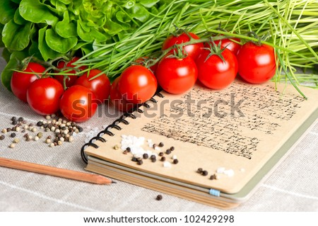 open vintage cook book  with old recipe text. vegetables tomato, chives and spices