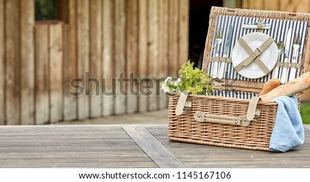Open vintage fitted picnic hamper with baguettes outdoors on a rustic table near a wooden cabin with space alongside for placement of food in panorama format Stockfoto ©