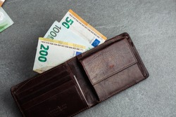 Open wallet with euro currency on grey phone.  Money. euro cash background. Euro Money Banknotes. Pile of paper euro banknotes as part of the united country's payment system. horizontal photo