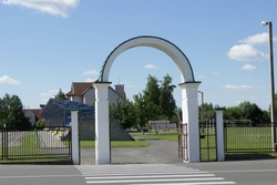Open white arched gate with a fence located in the city recreation park, stadium, athletic field. Summer blue sky with white clouds.