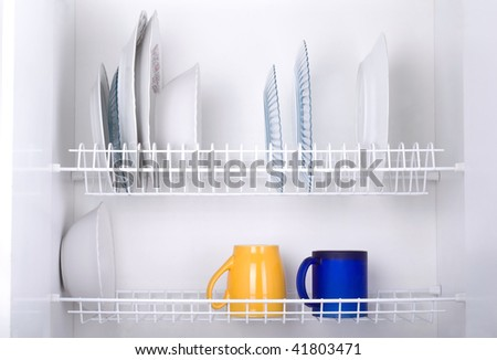 Open white dish draining closet with wet dishes of glass and ceramic, plates, bowls, covers and mugs objects drying inside on rack made of plastic coated steel wire and open bottom