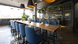Open wooden bar counter with alcohol on shelves in modern cafe, restaurant interior, panorama, copy space