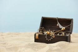 Open wooden chest with treasures on sandy beach, space for text