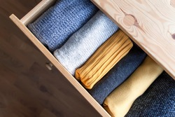 Open wooden dresser drawer with warm knitted woolen clothes. Home vertical storage. Wardrobe organisation. Trendy colors.