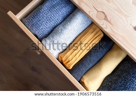Open wooden dresser drawer with warm knitted woolen clothes. Home vertical storage. Wardrobe organisation. Trendy colors. Foto stock ©