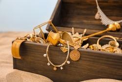 Open wooden treasure chest on sandy beach, closeup