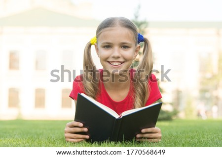 Open your imagination, read. Happy kid read book on green grass. Developing imagination. Childhood imagination. Imagination and fantasy. Cognitive reading skills. Summer reading. Become imaginative.