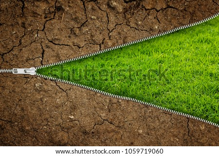 Open zipper with dry soil on fresh green grass with copy space for your text- Ecology concept.