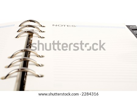 Opened agenda with the notes word written, over a white background. Small DOF