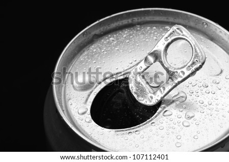 opened aluminum can with water drop on black background