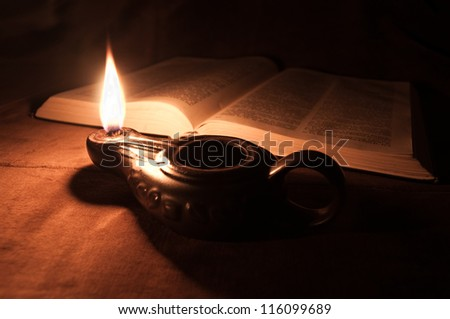 Opened Bible and Oil Lamp