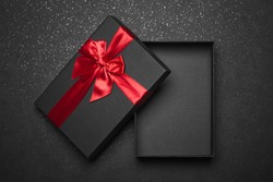 Opened black gift box with a red ribbon and a large bow on a dark granite surface. Empty box. Mockup
