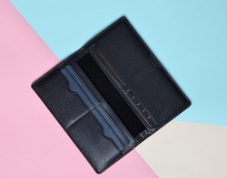 Opened blank black purse on a pastel background. Trend of minimalism. Top view.