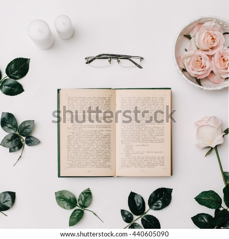 Opened book, glasses, pink roses on white background. Flat Lay