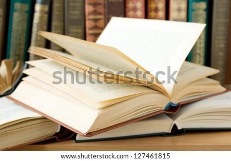 Opened book lying on the bookshelf