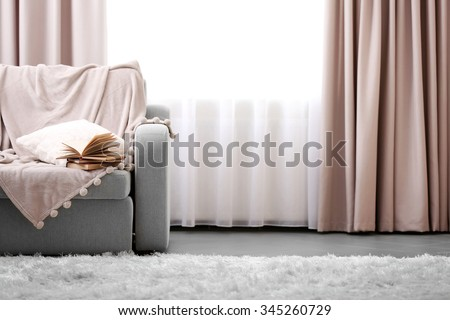 Opened book on comfortable sofa against window in the room
