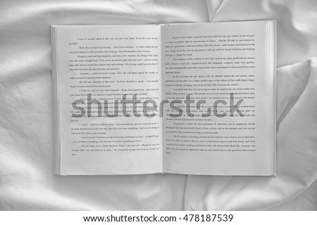 Opened book on white crumpled sheet #478187539
