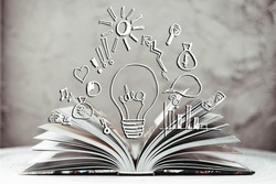 Opened book with business sketches and painted bulb as a concept idea over background