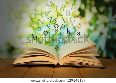 Opened book with letters flying out of it on bright background - stock ...
