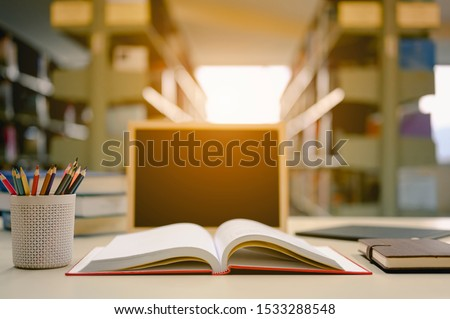 Opened book with pencil box and blackboard on the desk wood in the library prepare for new knowledge.  Education background concept.