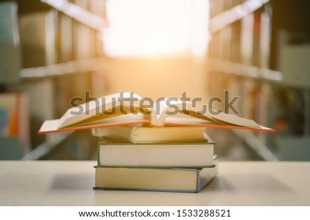 Opened book with stack of books on the desk wood in the library.  Education background concept.