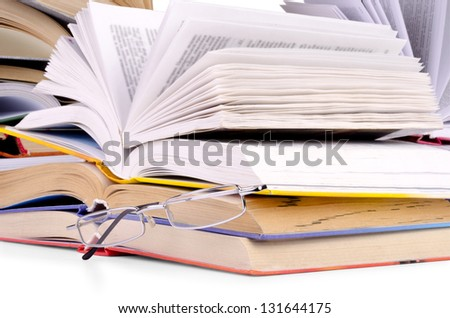 opened books and glasses on table front of a full bookshelf