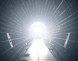 Opened cargo module of a spacecraft with light at the end. Light at the end of tunnel.