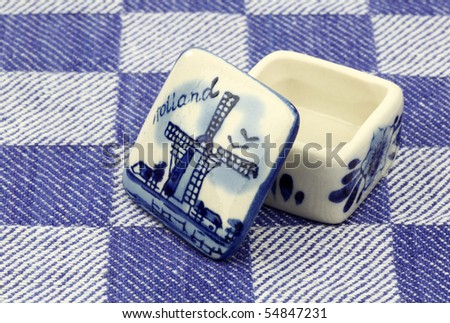 Opened ceramic delft blue pill box on a blue checkered kitchen towel