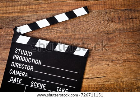 Photo of  Opened clapper board or slate film on wooden background.