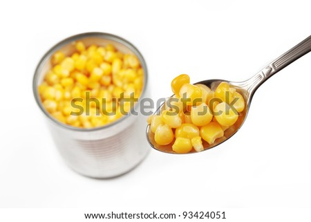 opened corn can with spoon filled with cond, isolated on a white background